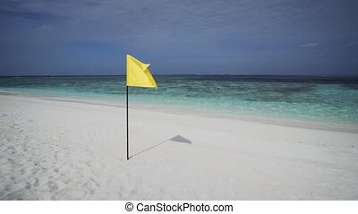 Yellow Flag Flaps over Tropical Beach Paradise in the...