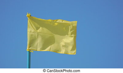 Yellow flag flutters in the wind - The yellow flag flutters...