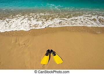 yellow flippers on sand beach