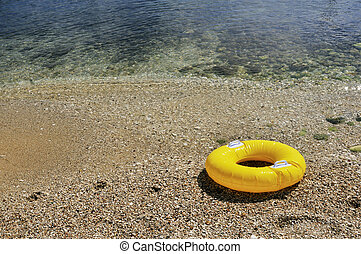 Yellow floating toy at the beach