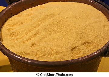 Yellow flour in old copper cauldron