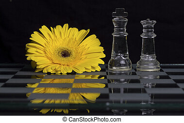 Yellow flower on black and white glass chess board with king and queen