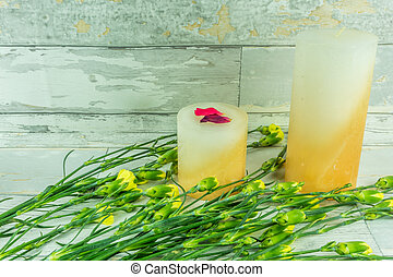 Yellow flowers with candles on a background of wood