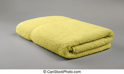 Yellow folded bath towel on gray background with copy space