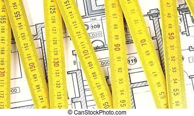 Yellow folding rule on building plan, rotation - Yellow...
