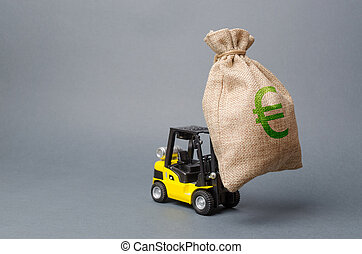 Yellow forklift truck carries a big bag of money. Attracting investment in development, modernization of production and business. Revenue, profit, liquidity. profit point fixation. capital migration