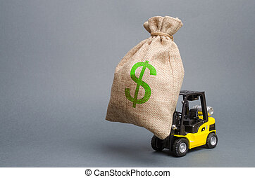 Yellow forklift truck carries a big bag of money. Attracting investment in the development and modernization of production and business, infrastructure projects. Revenue, profit, sales and liquidity.