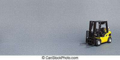 Yellow forklift truck on gray background. Warehouse equipment, vehicle. Logistics and transport infrastructure, industry and agriculture. Unloading, transportation, sorting. Banner, copy space