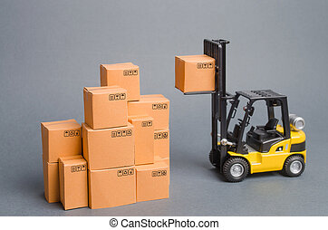 Yellow Forklift truck raises a cardboard box to the top of a stack pile of boxes. Warehouse, stock. commerce, retail. E-commerce, sale of goods through online trading. Freight shipping, deliver.