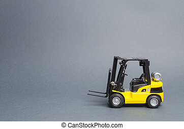 Yellow forklift truck side view on gray background. Warehouse equipment, vehicle. Unloading, transportation, sorting, loading cargo. Logistics and transport infrastructure, industry and agriculture