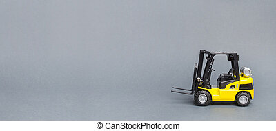 Yellow forklift truck side view on gray background. Warehouse equipment, vehicle. Unloading, transportation, loading cargo. Logistics and transport, industry and agriculture. Banner, copy space
