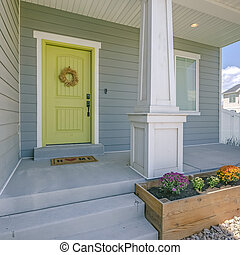 Yellow front door of a home with stairs and porch