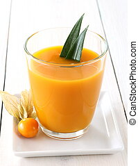 Yellow, fruity mango smoothie made from ripe fruit, physalis...