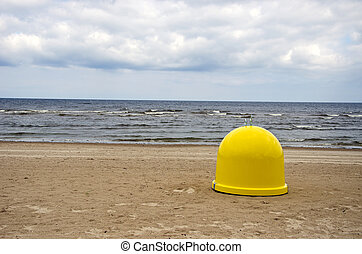 yellow garbage box on beach sand and sea