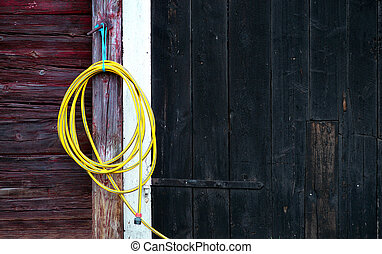 Yellow garden hose hanging on wooden wall