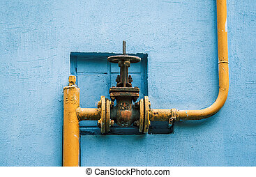 yellow gas pipe with a valve on the blue wall