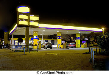 yellow gas station with cars and people at night