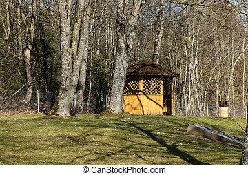 Yellow gazebo in the park in spring