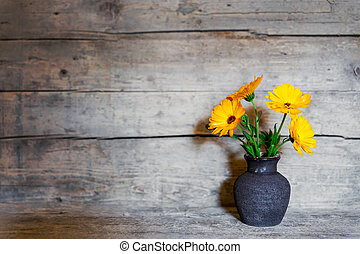 yellow gerbera in a old vase on wooden background