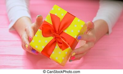 Yellow gift box in female hands. Young woman hands with...