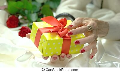Yellow gift box in female hands. Well-groomed hands of...