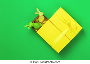 Yellow giftbox with two bunnies on green background