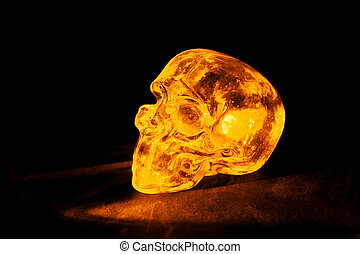 Yellow glass skull - Transparent glass skull lit with...