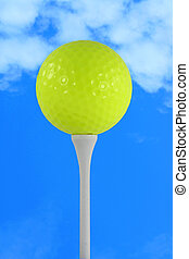 Yellow golf ball against blue sky