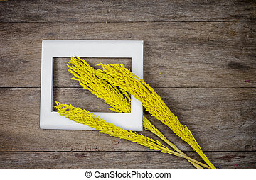 Yellow grass flowers on wooden background