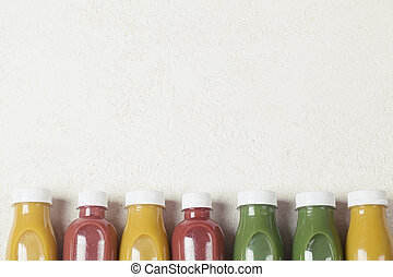 yellow green and crimson smoothie on white background, served in bottle