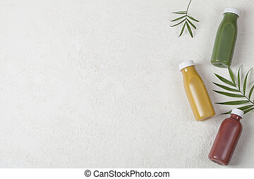 yellow green and crimson smoothie on white background, served in bottle with palm leaf