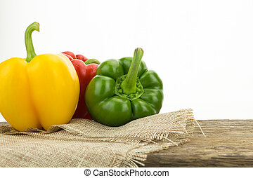 Yellow, green and red bell peppers on wooden surface, on white background with copy-space