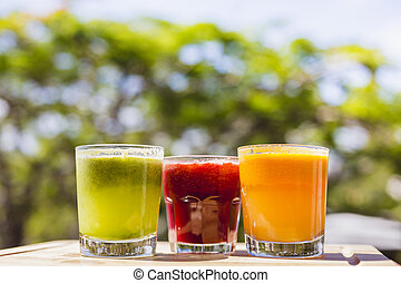 Yellow, green and red fruit and vegetable juices in tumbler glas