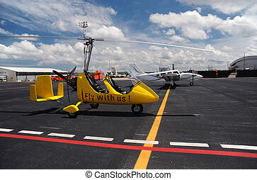 Yellow gyroplane in the international airport - Yellow...