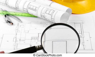 Yellow hard hat and a plan turning