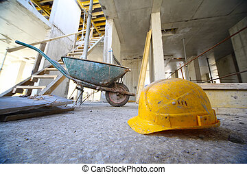 Yellow hard hats and small cart on concrete floor inside...
