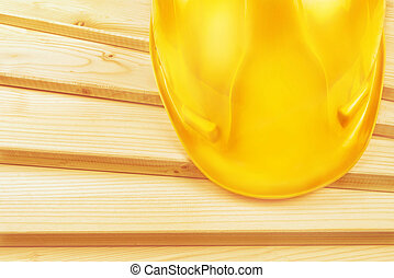 Yellow hardhat on pine wood planks