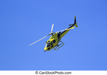 yellow helicopter in a blue sky