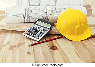 Yellow helmet with blueprints and calculator on wood