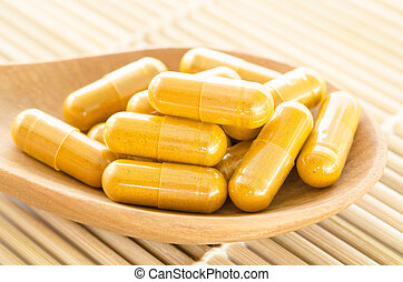 Yellow herb in wooden spoon