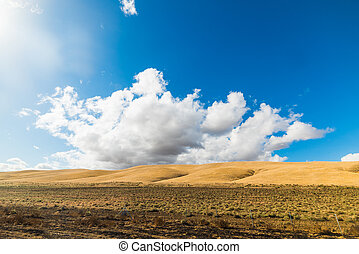 yellow hill under a blue sky with clouds