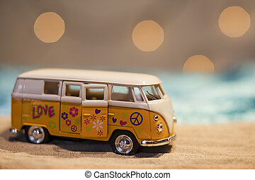 Yellow hippie van with peace sign on a sandy beach