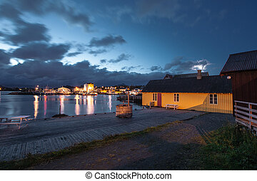 Yellow house and mirror lake with view to city and sea in the Norway at summer at sunset
