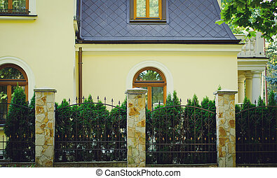 yellow house facade with fence and green trees