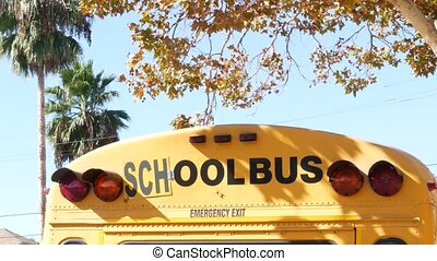 Yellow iconic school bus in Los Angeles, California USA. Classic truck for students back view. Vehicle stoplights for safety of children transportation. Public passenger transport for kids in suburb.
