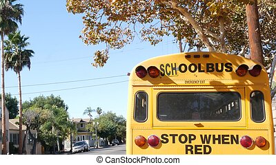 Yellow iconic school bus in Los Angeles, California USA. Classic truck for students back view. Vehicle stoplights for safety of children transportation. Public passenger transport for kids in suburb
