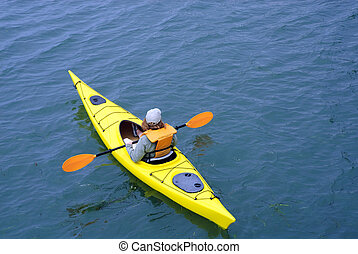woman in yellow kayak with yellow paddles leaving dock at Morro Bay