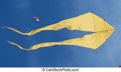 Yellow kite with two tails hovering in blue sky and sunny day