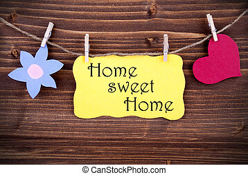 Yellow Tag Or Label With Heart And Flower On A Line With Life Quote Home Sweet Home On Wooden Background, Two Symbols, Vintage, Retro And Old Fashion Style With Frame
