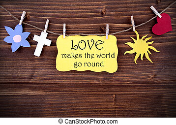 Yellow Tag Or Label With Heart And Flower And Cross And Sun On A Line With Life Quote Love Makes The World Go Round On Wooden Background, Four Symbols, Vintage, Retro And Old Fashion Style With Frame